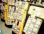Some of the racks I keep my tapes stored on in my garage studio. They came from my job in the grocery store and originally held Duracell batteries. 75 tapes fit into each one of the kiwifruit boxes you see pictured and they all revolve for easy access.